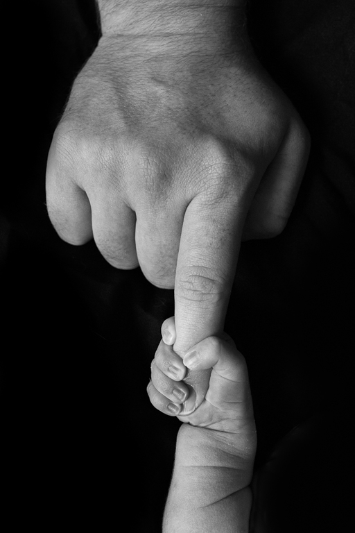 This is a newborn photography image in Huntsville, AL of a newborn grasping daddy's finger