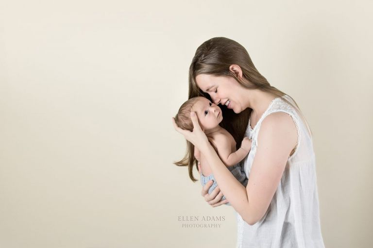 This is a newborn photography image of a mom holding her older newborn baby, photographed by Ellen Adams Photography.