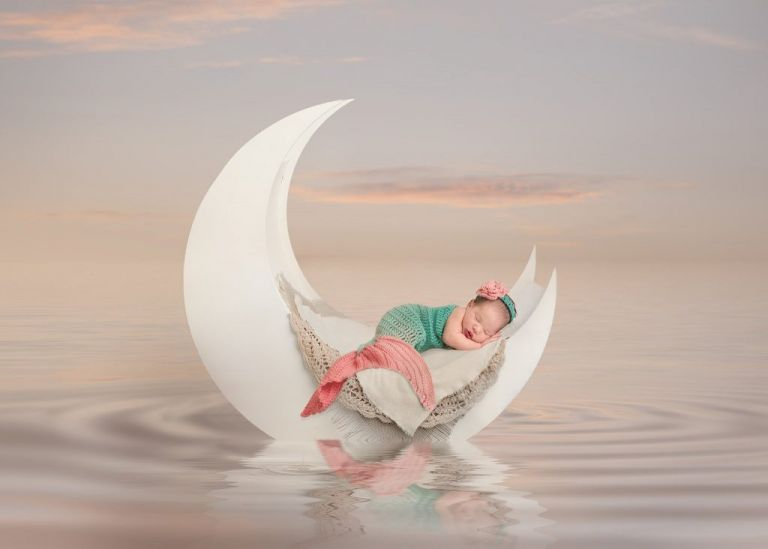Huntsville newborn photography picture of 11 day old baby dressed as a mermaid in the sea, captured by Ellen Adams Photography.