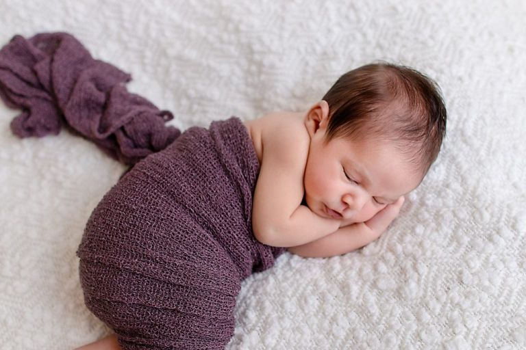 Newborn photography in Huntsville, AL image of baby wrapped in purple swaddle