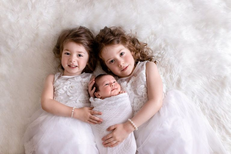 Image of sisters with newborn photograph in Huntsville, AL