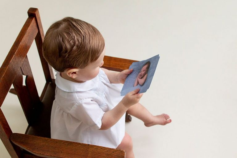One year old looking at picture of himself as a one day old, by Ellen Adams Photography