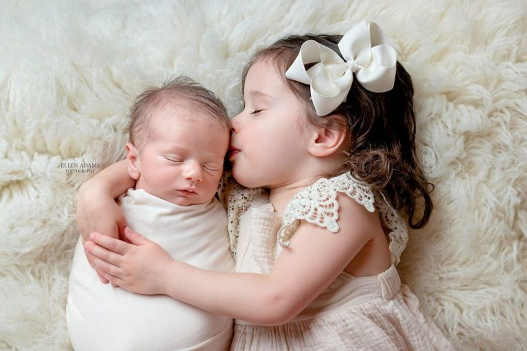 Newborn photographer in Huntsville, AL, Ellen Adams Photography, photographed this image of a newborn baby kissed by his big sister.