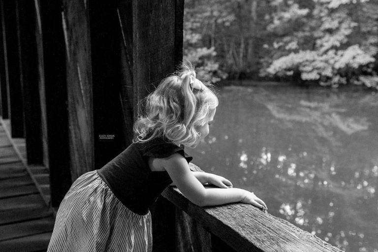 Little girl looking out of a window in a covered bridge.