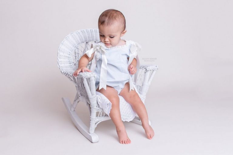 Baby photos of Madison AL with a baby sitting in a white wicker chair by Ellen Adams Photography.