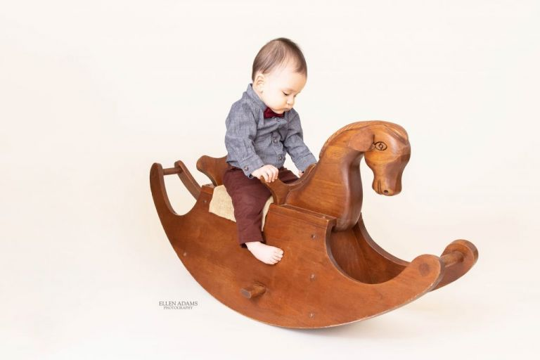 Baby riding a rocking horse by Ellen Adams Photography.
