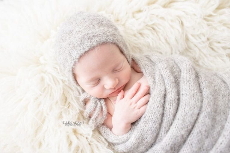 Newborn photography in Huntsville, AL image of baby wrapped in gray swaddle